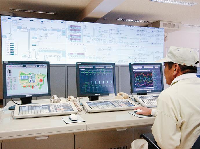 情報の一元管理を実現したIndustrial-DEO。トレンドグラフを常時表示し、運用データの異常を早期に発見し処置を行う。後方の大画面表示装置では場外設備の浄水場やポンプ場・配水池の状態を表示し、オペレータ間で情報の共有を図っている。
