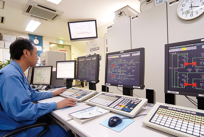 計器室内にはHarmonasとPREXIONが並べて設置されている。大型モニタには、製造しているガスの分単位での原単位や、1時間当たりの電気消費量などの動向がリアルタイムで表示されており、オペレータ全員で情報を共有し適切な対応を行っている。
