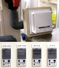 実験棟内の湿度を計測している室内型湿度センサ ネオスタット(上)と、室内温度、CO2濃度、溶液温度を制御するデジタル指示調節計 SDC25(下)。