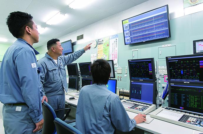 アノン製造プラントの集中監視を行う計器室。APS5000の監視・制御端末の上方には、65インチ大型モニターを設置。平常時にはAPS5000などの監視画面を表示し、警報発生時にはACTMoSの監視画面が強制表示される。警報が発せられた際には現場のメンバー全員が画面を見て状況を共有し、対処に向けた連携が取れるようになっている。