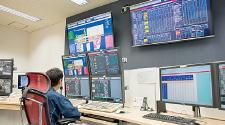 有明南プラントの中央監視室の様子。台場、青海南、有明南の各プラントでは、他プラントの中央監視の画面を参照できるようにした。これにより他プラントで発生したトラブル対処にかかわる情報も共有できる。また、運転支援画面には、現在1GJ(ギガジュール)の熱生産に要している電気、ガスの消費にかかわるエネルギー料金の概算を「××円」の形で画面表示する、というユニークな仕組みも実装されている。左)