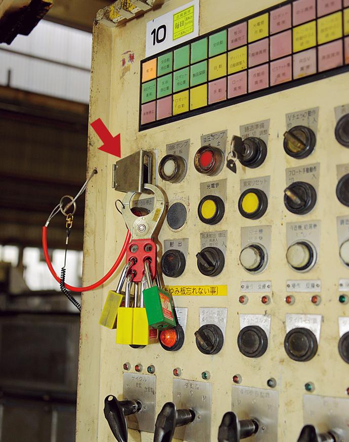鋳造機の操作盤電源スイッチ部分に取り付けられた金属板カバーとパドロック(南京錠)。ロックアウト用掛け金を用いることで、6人までのパドロックを使用することができ、すべての作業者が鋳造機内から退去してパドロックが取り外されるまで、動力を再開することができない。これにより各作業者の安全が確保される。この鋳造機では、鋳造課が3人、金型課もしくは工務課が1人の計4人が作業を行っているということも一目で分かる。