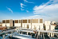 建物屋上に設置された8台のGHPエクセルチラーとマイクロコージェネ。GHPエクセルチラーは通常時8台で最適運転を行い、故障時にはバックアップ運転を行う。マイクロコージェネは、排熱を風呂などの給湯に利用している。