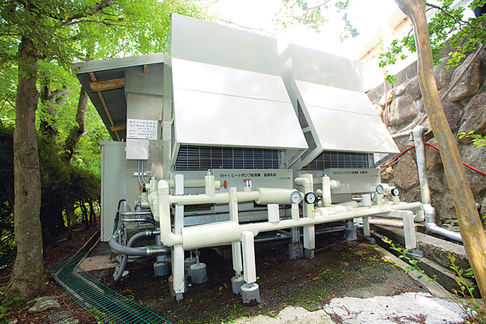 今回導入されたヒートポンプ給湯器。安価な深夜電力を利用して蓄熱を行う。旅館は夕方にエネルギー消費のピークを迎えるため、不足分や急激な負荷変動については既設のガス焚き真空温水器で追いかけ運転を行うことができるハイブリッド方式へ更新した。