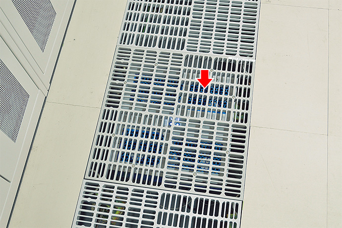 サーバルーム内の各所に設置されている床冷却ファン(グリルパネルの下)。その配置は、アズビルの熱気流シミュレーションに基づく分析により決定されており、二つのサーバルームに計34台のファンが設置されている。