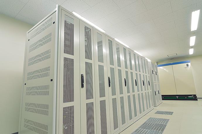 顧客から預かったサーバを設置するラック(手前)とサーバから出る熱を冷却するための空調機(奥)。
