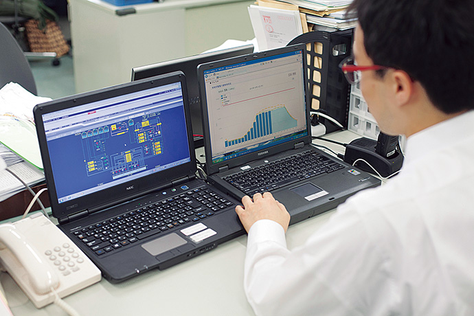 事務所のデスクに置かれたパソコンから中央監視システムの監視画面やWeb-Infilexの電力消費動向画面を確認。現地の中央監視室に行かなくても状況を把握することができる。