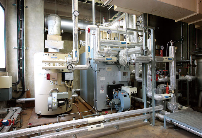 今回導入した高効率ボイラ(右)と旧来の重油焚きボイラ(左)。重油焚きボイラは、ヒートポンプ給湯器が故障したり、お湯の要求量が能力を超えた場合の追従運転用となっている。