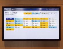 学生ホールに設置された教員の在室状況を表示する液晶ディスプレイ。各教職員の「在室」「学内(講義中)」「外出」「不在(帰宅)」を表示している。また、画面のレイアウトや色使いなどは、ユニバーサルデザインに基づいて設計されており、色覚障がい者にも容易に視認できるよう工夫されている。
