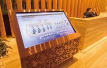 Gaysorn Towerのオフィスフロア受付横に設置されたデジタルサイネージ。普段はインフォメーション画面が表示されているが、Gaysorn Towerのビル管理に関する見学を受け入れた際などに、savic-net G5の監視画面へ表示切替えができるようになっている。