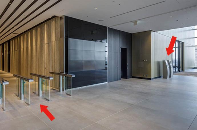 オフィスフロアへの入り口に設置されたセキュリティゲートと来訪者管理システムの無人発券機。