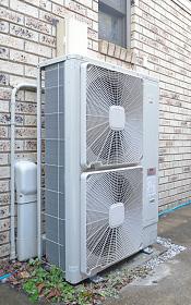 屋外に設置された室外機。旧型に比べ効率が良くなり消費電力が少なくなっている。