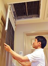 天井面に設置された電子式エアクリーナ。開閉グリルを開いて、中のプレフィルタ表面のホコリを掃除機で吸い取るだけなので、日常のお手入れも簡単。