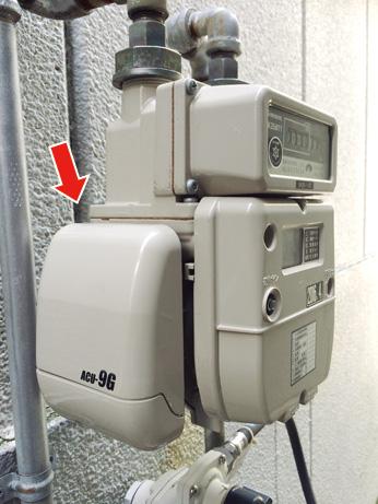 顧客宅のガスメーター脇に取り付けられているアズビル金門のLPガス集中監視用通信装置。この通信装置からACU集中監視センターに情報が伝送される。